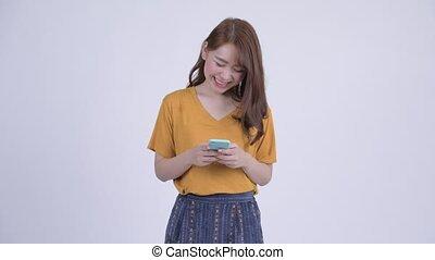 Happy young beautiful Asian woman using phone