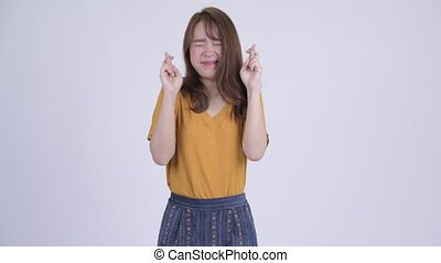 Happy young beautiful Asian woman wishing with fingers crossed