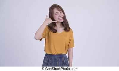Happy young beautiful Asian woman with call me gesture