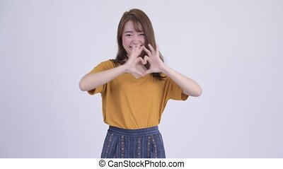 Happy young beautiful Asian woman with hand heart gesture
