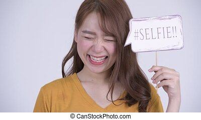 Happy young beautiful Asian woman with selfie paper sign