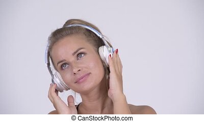 Happy young beautiful blonde woman listening to music
