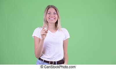 Happy young beautiful blonde woman pointing at camera -...