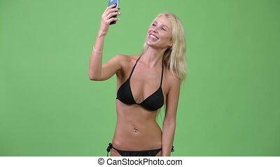 Happy young beautiful blonde woman wearing bikini while video calling