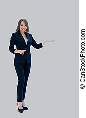 Happy young beautiful business woman showing blank area for sig