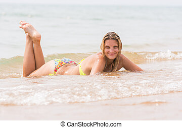 Happy young beautiful girl lies on the beach