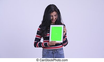 Happy young beautiful Persian woman showing digital tablet -...
