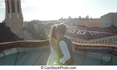 Happy young beautiful stylish couple bride and groom hugging gently on the roof at sunset city street in the background
