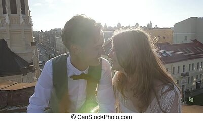 Happy young beautiful stylish couple bride and groom kiss gently on the roof at sunset city street in the background