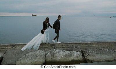 beautiful stylish couple bride and groom walking along the embankment at dusk, slow motion