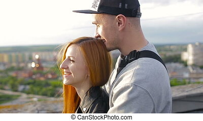 Happy young beautiful stylish couple hugging each other on the roof of the house