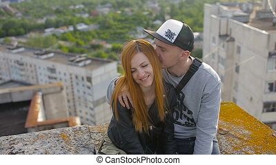 Happy young beautiful stylish couple hugging on the roof of the house