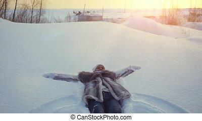 Happy young beautiful woman falling down in winter lying in...