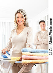 Housework - Happy young beautiful woman ironing clothes. ...