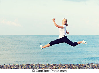 happy young beautiful woman jumping at beach on the Sea