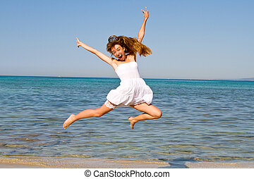 Happy young beautiful woman jumping on the beach