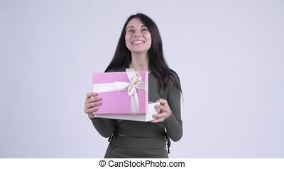 Happy young beautiful woman opening gift box and looking...