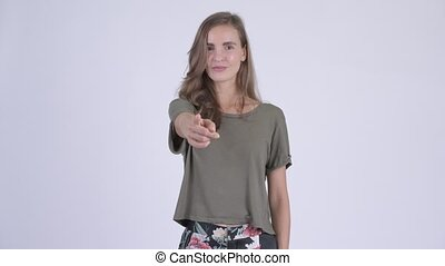 Happy young beautiful woman pointing at camera