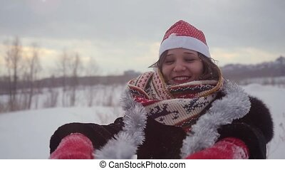 Happy young beautiful woman wearing christmas hat having fun outdoors in winter snowy nature in slow motion. 1920x1080