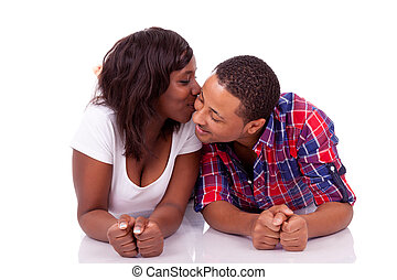 Happy young black African American couple lying down on the floor, isolated on white background - african people