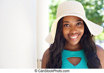 Happy young black girl with long hair and sun hat