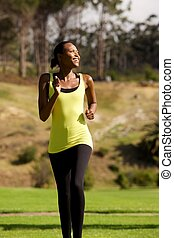 Happy young black woman running in park