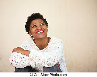 Happy young black woman smiling and looking up