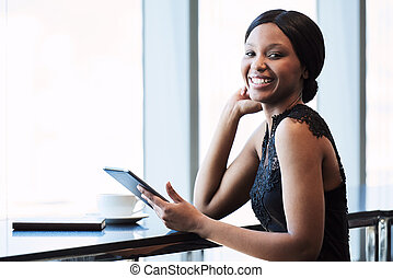 Happy young black woman smiling at the camera with tablet