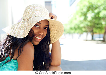 Happy young black woman smiling with sun hat outdoors