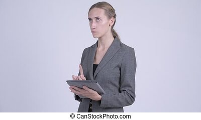 Happy young blonde businesswoman thinking while using...