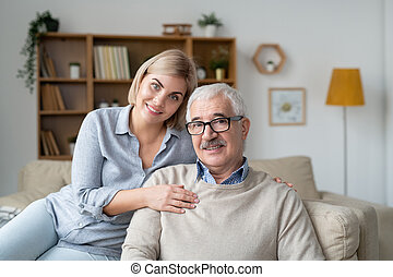Happy young blonde female and her father in casualwear relaxing on couch at home