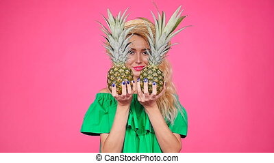 Happy young blonde woman holding a two pineapple on a pink...