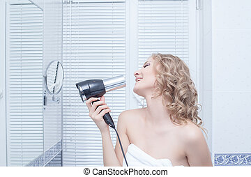 Happy young blonde woman singing in bathroom