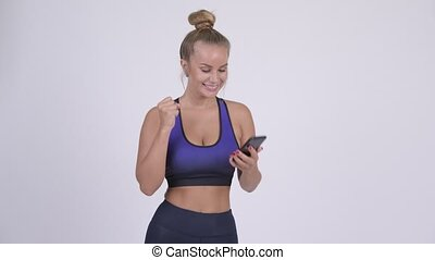 Happy young blonde woman using phone and getting good news -...