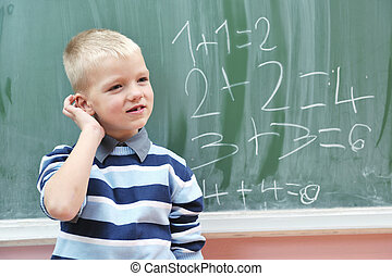 happy young boy at first grade math classes solving problems...