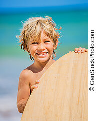 Happy Young boy having fun at the beach on vacation, with skimboard