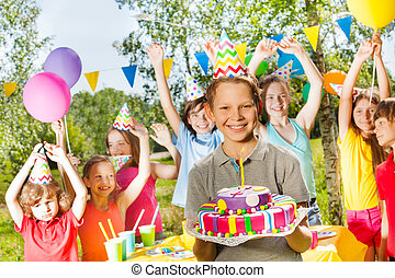 Happy young boy in party hat holding birthday cake