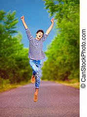 happy young boy jumping on summer road