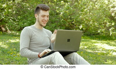happy young boy laughing and working with laptop