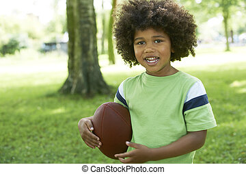 Happy Young Boy Playing In Park With American Football