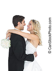 Happy young bridegroom hugging his wife