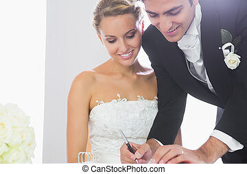 Happy young bridegroom signing wedding contract