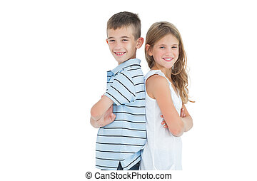 Happy young brother and sister posing back to back