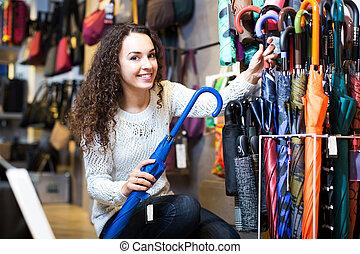 Happy young brunette choosing umbrella