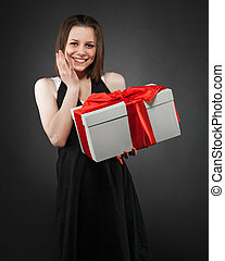 Happy young brunette girl with present