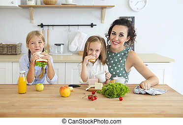 Happy young brunette mother with cute little kids having breakfast