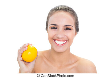 Happy young brunette woman holding an orange