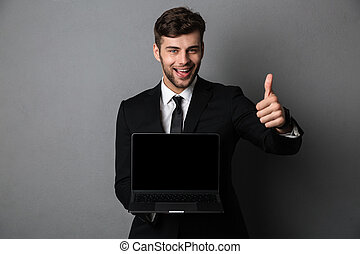 Happy young business man showing thumbs up gesture.
