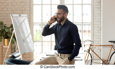 Happy young business man talking on phone in office room