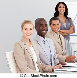 A business team sitting and smiling at the camera